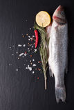 Fresh fish, lemon, pepper and rosemary on a black background. Ti Stock Image