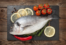 Fresh fish, lemon, spices and cherry tomatoes on a stone board Stock Photo