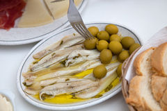 Fresh Fish Meat on White Plate with Olives. Close up Fresh Fish Meat on White Plate with Green Olives Served on the Table Stock Photo