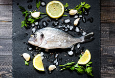 Fresh Fish Orata Over a Black stone with vegetables Royalty Free Stock Image