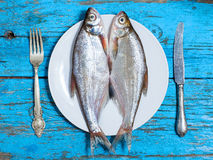 Fresh fish on the plate, table setting, wooden background Stock Photos