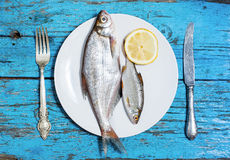 Fresh fish on the plate, table setting, wooden background Stock Photography