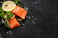 Fresh fish portions with lemon slices, rosemary, parsley, salt and peppercorns on a black stone background, Stock Image