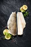 Fresh fish,  raw cod fillet with addition of herbs and lemon slices on black stone background. Top view Royalty Free Stock Photos