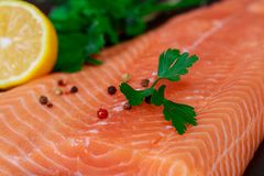 Fresh fish, salmon fillet with vegetables top view, tasty and healthy food. Of lemon and fresh leaves royalty free stock image
