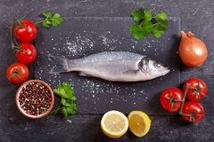Fresh fish sea bass with ingredients for cooking. On dark background, top view Stock Photography