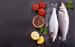 Fresh fish sea bass with ingredients for cooking. On dark background, top view Royalty Free Stock Photography
