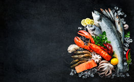 Fresh fish and seafood. Arrangement on black stone background stock photo