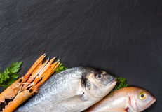 Fresh fish and seafood. On dark vintage board Stock Photo