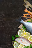 Fresh fish and seafood. Fresh fish with seafood and vegetables on a wooden board isolated on white Stock Images