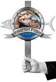 Fresh Fish - Sign with Hand of Chef. Hand of chef holding a metal sign with fresh fishes, blue waves and metal ribbon with text Fresh fish. Isolated on white Stock Photography