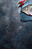 Fresh fish with spices on a stone board. Fresh fish with chilli isolated on a stone board Stock Images