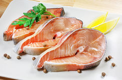 Fresh fish, steaks fish, red fish on a plate on a wooden background Royalty Free Stock Photography