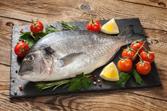 Fresh fish with tomato and lemon on old table Royalty Free Stock Photography