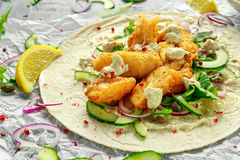 Fresh Fish Tortilla with cucumber, red onion, Capers, lemon, salad leaves and tartare sauce. Healthy Food Royalty Free Stock Photos
