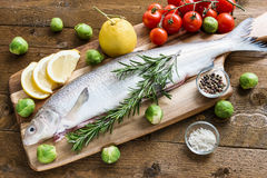 Fresh fish with vegetables on wooden board. Top view. Royalty Free Stock Images