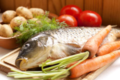 Fresh fish on a wooden board with vegetables Stock Photo