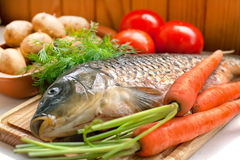 Fresh fish on a wooden board with vegetables Stock Images