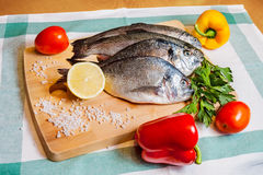 Fresh fish on wooden cutting board Royalty Free Stock Photos