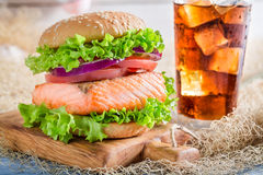 Fresh fishburger with salmon served with cold drink Royalty Free Stock Photography