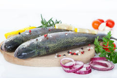 Fresh fishes with spices and vegetables. Fresh fishes with spices and seasoning on cutting board Stock Photo