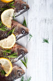 Fresh fishes tails with lemon. Fresh river fishes with lemon on a wooden white background close up Stock Photography