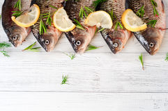 Fresh fishes tails with lemon. Fresh river fishes with lemon on a wooden white background close up Stock Images