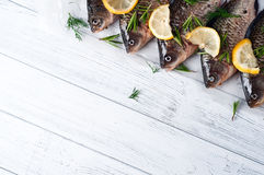 Fresh fishes tails with lemon. Fresh river fishes with lemon on a wooden white background close up Royalty Free Stock Photo