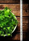 Fresh Fitness salad and measuring tape on rustic wooden table. Royalty Free Stock Photo