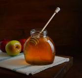 Fresh flavored honey in a large pot and a spoon, apples, napkin on a wooden background Stock Photos