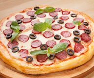 Fresh flavorful pepperoni pizza on wood Royalty Free Stock Photography