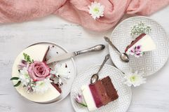 Fresh flowers decorated layered cake. Romantic fresh flowers decorated white cake and cut pieces in plates with vintage silverware on rustic wooden background stock photo