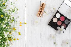 Fresh flowers, decorative cosmetics on a wooden background royalty free stock photo