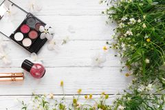 Fresh flowers, decorative cosmetics on a wooden background stock photos