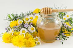 Fresh flowers and a jar of honey Stock Image