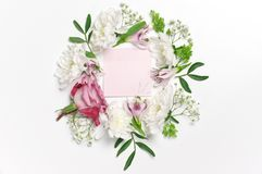 Romantic floral background. Fresh flowers and leaves composition as frame around pink notepaper on white. Romantic background, top view point stock images