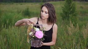 Fresh flowers in a stylish drawer. Beautiful brunette in a flowery field in the evening. Slim girl in black dress holds Gift floral arrangement stock footage