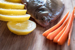 Fresh flunder with lemon and carrot Royalty Free Stock Photos
