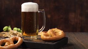 Fresh foamy Lager beer in a glass mug on a dark wooden table. Fresh foamy Lager beer in a glass mug on a dark wooden table with german pretzels stock video footage