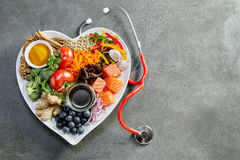 Fresh food for a healthy heart with a stethoscope. Fresh food for a healthy heart with acai, lentils, soy sauce, ginger, salmon, carrot, tomato, turmeric royalty free stock image