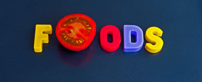 Fresh foods logo. Text ' foods ' in colorful uppercase letters with one letter Stock Photo