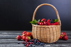Fresh forest berries in basket on rustic wooden background. Copy space Royalty Free Stock Photography