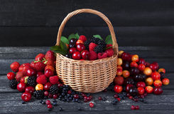 Fresh forest berries in basket on wooden background. Copy space Royalty Free Stock Images