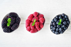 Fresh forest fruits. Fresh blueberries, raspberries and blackberries in bowl on old white wooden background, top viewselective focus Stock Photo