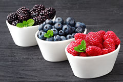 Fresh forest fruits. Fresh blueberries, raspberries and blackberries in a white bowl on old black wooden background, selective focus Stock Photos