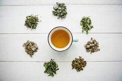Fresh fragrant and healthy herbal tea in a glass or mug on a white wooden surface. Next to it lie various dried herbs. For making tea. Healthy product royalty free stock images
