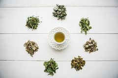 Fresh fragrant and healthy herbal tea in a glass or mug on a white wooden surface. Next to it lie various dried herbs. For making tea. Healthy product stock photo
