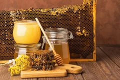 Fresh fragrant honey in a glass jar on a wooden background on the table. Different types of bee honey. Natural products. Fresh fragrant honey in a glass jar on stock photography