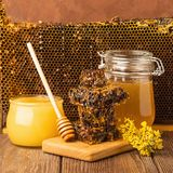 Fresh fragrant honey in a glass jar on a wooden background on the table. Different types of bee honey. Natural products. Fresh fragrant honey in a glass jar on royalty free stock photos