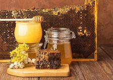 Fresh fragrant honey in a glass jar on a wooden background on the table. Different types of bee honey. Natural products. Fresh fragrant honey in a glass jar on stock images